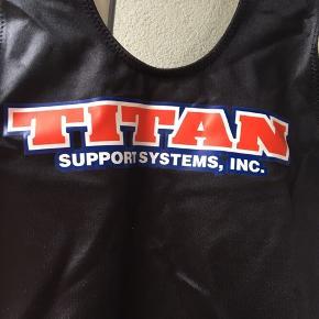 Vægtløfter/styrkeløfttrikot fra Titan i L med pink detaljer. Aldrig brugt. Købt fra officiel Titanforhandler.