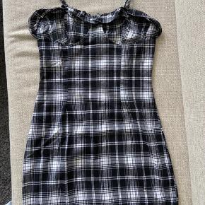 Sort/hvid ternet kjole med lynlås i ryggen. Mener den er fra H&M. Har aldrig været brugt, da den er for stor til mig.