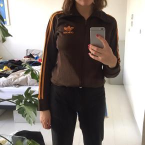 Flot brun Adidas trøje med lynlås og orange striber på ærmerne. Lidt 80'er/90'er model