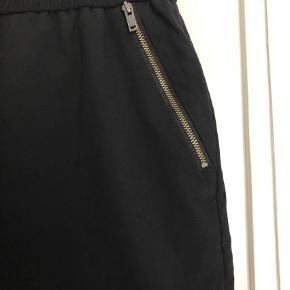 Varetype: Mariaa skirt Farve: Sort  Fin nederdel med flotte lynlås detalje.   Er blevet brugt en del, men stadig i fin stand.   70% viskose/15% bomuld/15% polyester.  Der står nederdelen skal renses - jeg har altid blot vasket den på håndvaskeprogram.   Bytter ikke!