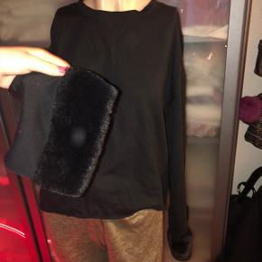 Almindelig sort trøje med faux fur pelsærmer. Det er lyset der laver en cirkel på første billede ✨