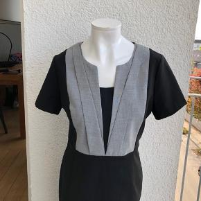 Flot kjole med fine detaljer - bla. leopardplettet inderfor. Materialet er 43% uld, 53% polyester og 4% elastan. Inderforet er af 94% polyester og 6% elastan. Mål er: Brystmål: ca. 2*47 cm Længde: ca. 100 cm Den er aldrig brugt, kun prøvet på :-) Min. pris 200 plus porto