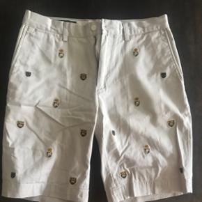 Cool shorts fra Polo Ralph Lauren af i beige med broderet skjold på. Modellen fås ikke mere og det er fra før der nye logo kom til. Størrelse 31 og går lige til over knæene i længden. De er aldrig blevet benyttet men kun prøvet på og derfor tog jeg mærkerne af. Kostede 1.399kr
