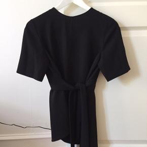 Smuk sort bluse med bindebånd fra Zara. Lukkes med trykknap i nakken. Giver den flotteste figur.