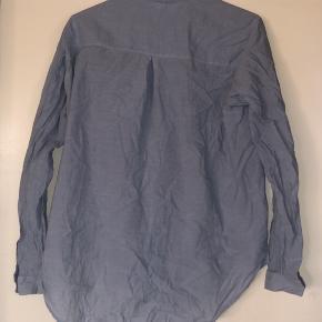 Fin lyseblå skjorte, lidt krøllet men i meget fin stand, ikke brugt mange gange. Stor i størrelsen, passer en S & M.