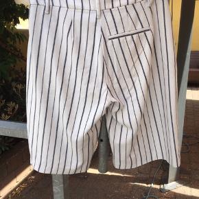 Flotte shorts i hvid med blå striber. Lommer i siden. Brugt tre gange. Dejlig let stof.