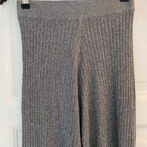 Flare glimmeragtige bukser i stretchy materiale. Har matchende cardigan/slå-om bluse til