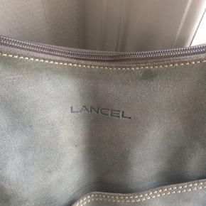 LANCEL skuldertaske i lyseblåt ruskind med camelfarvet læderstropper... camelfarvet  stof for. Sadelfacon. Guldmetal ringe i siden af taske, 2 lommer indvendig og lynlås i toppen. Ruskindet trænger til en rensning, men læderstropper og for er fuldt intakt og rigtig pæn stand... original dustbag medfølger.. B44 x L31/60cm... gerne mobilpay eller TS-handel +5%