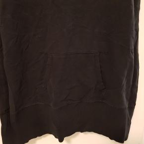 Lang sort træningstop i kraftig jerseystof med lomme nederst foran.  Mål Længde: 77cm Bredde: 47cm