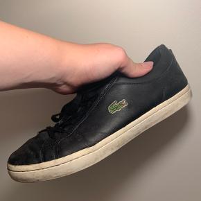 Jeg sælger mine Lacoste sko. Logo fremgår på begges skos yderside. Med en god klud og en god portion knofedt vil de nemt kunne shines op. Der er et hul i indersiden af skoen ved venstre hæl (se vedlagt billede) - dette mærkes dog ikke ved brug.