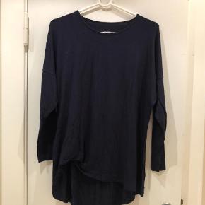 Varetype: Bluse Størrelse: S/M Farve: Blå  Lækker langærmet t-shirt fra Comfy Copenhagen sælges.   Den har rund hals, lidt rynkeeffekt foran i den ene side og længere bagpå end foran.   95% viskose og 5% elastan.   Køber betaler evt porto, der tillægges prisen. Jeg sender med Dao.