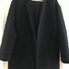 Den er mørkeblå med sort skind krave. Den er velholdt.