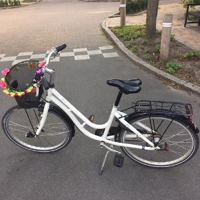 """KILDEMOES cykel, 24"""", med 7 gear. Kører rigtig godt. Lidt rust på bagagebærer og lidt revner i sadel, men sadel kan nemt udskiftes, eller man kan bruge sadelbetræk. Cyklen har magnetlygter, men kun den ene virker. Ikke forsøgt at reparere den anden. Cyklen har også lygter til batteri både for og bag. Cyklen har altid stået overdækket hjemme.  Den befinder sig i Odense C."""
