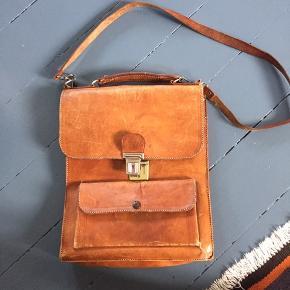 Unisex kernelædertaske med plads til A4-blokke. To store rum og to små. Den ene ring til stroppen er knækket, men virker fint alligevel.  Se også mine andre annoncer :)