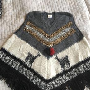 Super lækker poncho i baby alpaca uld fra Julie Fagerholt Heartmade. Skøn som jakke til foråret.  Tyk vamset uld og masser af møntpailletter som smykker på brystet.  Nypris 3000,- Mp 1000,- pp. BYD!