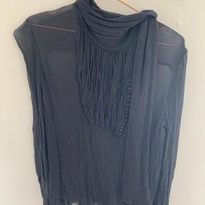 Flot mørkegrå gennemsigtig bluse med stofbetrukne knapper og krave/bindebånd. Mærket er desværre klippet ud, da det kunne ses igennem. Men stoffet minder om krep-stof. Aldrig været brugt, da det var et impulskøb.