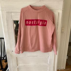Sweatshirt i lyserød med print. Blusen er brugt nogle gange.