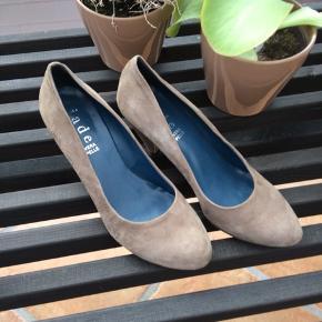 Skoene er brugt en enkelt aften som ses på foto. Hælen er 8 cm høj og de er helt normale i størrelsen. Farven er mørk beige/jordfarvet og skoene er lavet i ruskind