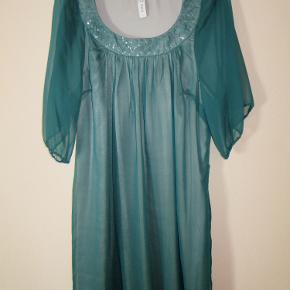 """Fin kjole i grønt gennemsigtigt stof med en silkeagtig grå underkjole, som """"skinner"""" lidt igennem det tynde, grønne stof og giver et sølvagtigt skær. Gennemsigtige ærmer som går ned til albuerne. Pyntet med palietter rundt om halsudskæringen. Længde fra nakke til underkant er 101 cm, fra udskæring til underkant er 92 cm. Nypris kr 700,- aldrig brugt."""