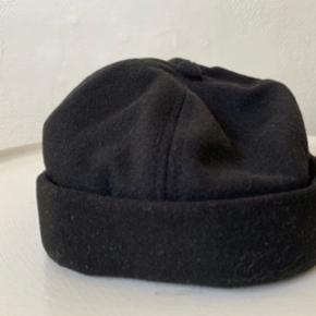Sort unisex docker hat fra UO i str. one size,  Kan reguleres lidt bagpå. Har den også i grå - se anden annonce. De to første billeder er af den jeg selv har i  brug og den nye ubrugte / indpakkede der sælges. Materiale er 90% poly og 10% blød uld. Sælges for ca 1/2 pris pp. Hvis brevpost via postnord kan Porto reduceres til 20