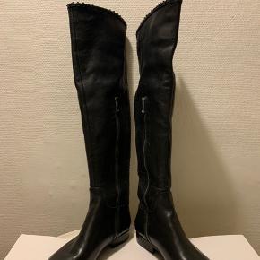 Sorte Lange knee / måske lidt over knee (afhængig af benlængde) støvler fra BDK i skind med phyton detaljer og lynlås på indersiden. Lille regulerbart spænde øverst på støvlens yderside. Total længde r ca 51 cm inkl hæl og omkreds øverst ca 37,5-38 cm Nypris pænt mere end 1000 Sål måler i længde udenpå 25,5 cm