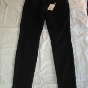 Superfede kulsorte, 5-lommet slim-fit-jeans i 73% bomuld, 23% polyester og 4% elastan med mørke nitter ned langs siderne og under linning for og bag. De er fra Zay = Zizzis luksusmærke. Størrelsen er 48, og de måler i taljen fra 96-110 cm. Ydersiden af benene måler 108 cm, indersiden måler 82 cm. Skridtlængden foran måler 30 cm og bagpå 44 cm. Benvidden forneden er 30 cm. Er splinternye med prsmærke. Virkelig både elegante og seje. Prisen var 899 kroner. Jeg sælger for 450 kroner.