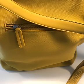 Super fed taske/cross body i karrygul og med logo på strop :-) Måler ca 37x31 cm og tasken har ét stort rum - stor lynlås lomme på den ene inderside og to mindre åbne lommer på modsatte side ( fin til mobil, etc ). Har aldrig været brugt - købt sidst på sommeren og 100 % ok