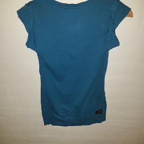 Lækker blød kortærmet t-shirt med fede detaljer så som lynlås på brystet, nitter på skuldrene, syninger på ryggen og bred kant forneden.