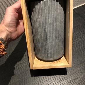 Lyngby Jubilæumsvase 20 cm sort marmor 1936 - 2016   Lyngby vasen kan i 2016 fejre sin 80 års fødselsdag og for at fejre den runde fødselsdag har Lyngby lavet en særlig jubilæumsudgave i portugisisk marmor.  Lyngby vasens eksplosive comeback de seneste år har gjort den stilrene vase til et designikon med den stramme, klassiske form, og det sorte portugisiske ruivina marmor fremhæver den doriske søjleform til perfektion. Den blankpolerede overflade giver marmoren en blød silkemat overflade, som man bare må røre ved, og den naturlige hvide marmorering, som er forskellig fra vase til vase, gør hver eneste marmorvase til et unikum.  Lyngby Jubilæumsvasen i marmor er fremstillet i Portugal, og hver enkel marmorvase er forskellig i sin karakter, idet marmoret har et forskelligt mønster.     Producent: Lyngby A/S Mål: 20 cm H x 11 cm B Materiale: Portugisisk ruivina marmor EAN: 5711841293555 Emballage: Jubilæumstræboks med tryk
