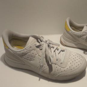 Varetype: Sneakers Farve: HVID Oprindelig købspris: 1200 kr.  Kun brugt få gange, købt i september 2018. Højaktuelle. Hvid ruskind med gult nikemærke i skind på hæl. Virkelig fine! Kom med et bud.