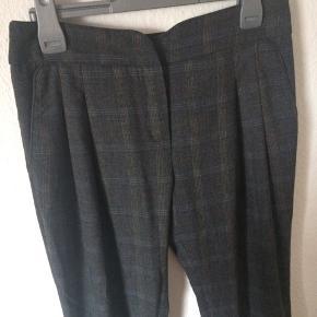 Mango suit - klassiske bukser Str. 36 Næsten som ny Farve: mørkegrå med tern (se billeder) Lavet af: 53% viscose, 45% polyester og 2% elasthane Mål: Livvidde: 76 cm hele vejen rundt Længde: Ydre: 106 cm Indre: 84,5 cm Køber betaler Porto!  >ER ÅBEN FOR BUD<  •Se også mine andre annoncer•  BYTTER IKKE!