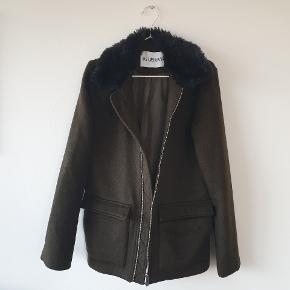 Wool air Jacket fra Han Kjøbenhavn. Af varm uld og med pelskrave. Jakken har en inderlomme og knaplås på yderlommerne. Jakken er kun prøvet og ikke brugt.