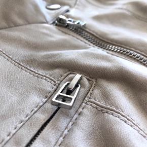 DAWN SHORT PU JACKET SN  Farve: Cream.  Brugt en sommer og har ligget i skabet siden. Den krakelerer en smule, men er ellers fin.  For flere billeder se i kommentar.  - Short PU jacket.  - Two front pockets.  - chest pocket with zip closure.  - Zipper closure at front.  - Tight fit.  - Top stitched details on the shoulders.  - Length: 53 cm in size S.  SHELL: 100% Viskose.  LINING: 100% Polyester.  Se også mine andre annoncer ;)