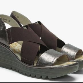 """Ny pris: Nu kun 450 kr inkl pakkeporto! Du kan få fat i disse skønne ubrugte sandaler fra Fly London til halv pris af nypris. Men kun, hvis du er hurtig. Jeg har nemlig købt dem på en engelsk webshop og sender dem retur om ca 1 uge, hvis der ikke er en, som vil overtage dem. Det er en ret alm. str 39 med skøn pasform pga elastikkerne og kile-/plateausålen. De er brune og bronzefarvede og har en cool kant, synes jeg, samtidig med, at de har Fly Londons gode pasform. MEN: De er desværre for smalle foran til min meeeget korte, brede, """"firkantede"""" fod. Mega-øv. Jeg plejer ellers at kunne bruge 39 i sandaler, men skal typisk have str 40 i lukkede sko & støvler pga min brede forfod. SÅ: De ryger retur til England, hvis ikke du vil købe dem.  Jeg vil gerne have 500 plus porto for dem."""
