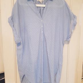 Kortærmet hvid- og blåstribet oversize skjorte med opsmøg på ærmer. 100% bomuld. Har den også i hvid - se min profil.  Mål Længe: 78cm Bredde: 64cm