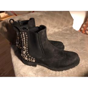 Rå støvle med nitter og bling bling. Støvlen har et bredt elastik i begge sider af skaftet. Støvlerne er i et kraftigt materiale der minder om ruskind. De er helt nye og ubrugte.