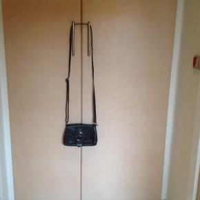 Lille fin håndtaske/skuldertaske. Måler 12 x 18 cm Justerbar rem Lukkes med magnetlukning