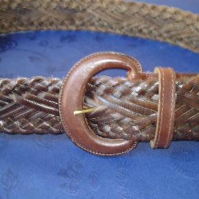 Varetype: Flettet brunt læderbælte 95 cm langt og 5 cm bredt Størrelse: 95X 5 cm Farve: Brun  Flot flettet brunt læderbælte, der er 95 cm langt og 5 cm bredt. Brugt et par gange og fremstår i meget flot stand. BYTTER IKKE!