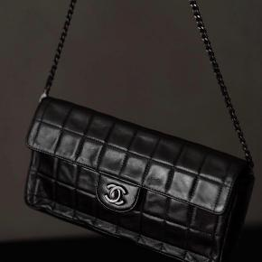 """Vintage Chanel East West bag in black lambskin leather🖤  Alle billederne er af min taske 👜  Details: This bag was produced in 2000/2002. It features dark mat silver hardware including the iconic CC turn lock. The chain is shoulder length and has a clasp in one side to make it into a clutch. The bag is made in soft lambskin leather and has a lining of pink satin. There is no damage or tears on the bag and no stains to the interior. Overall a very sexy classic bag in great vintage condition. •Serial code is intact as well as a """"made in France"""" fabric tag.  •Measurements: Length 27 cm Height 16 cm Width 4 cm"""