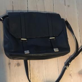 Cross-body skuldertaske fra Marc by Marc Jacobs. Kan have en lille laptop. L: 28,5 cm / H: 21 cm / D: 9 cm.  Tasken er i god stand, men med få slidmærker i bunden, på spænderne og remmen.