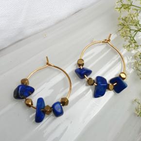 Hjemmelavede øreringe med små lapis lazuli flakes og metalperler, på nikkelfri guldtone hoops, diameter 2,1 cm.  Æske kan tilkøbes for 5 kr.