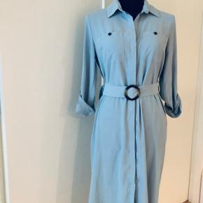 Helt ny lyseblå kjole med et bælte. Bæltet kan tages af og evt udskiftes med et andet. Kjolen kan knappen og også bruges som cardigan, for at få mest muligt ud af den.  Fine detaljer med knapper ved ærmerne og lommerne ved brystet
