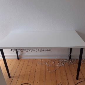 Hvidt skrivebord med sorte justerbare ben og lidt brugs ridser  Mål:  længde = 150 cm  Bredde= 75 cm   Afhentes senest indenfor den næste uge. Åben overfor andre bud.