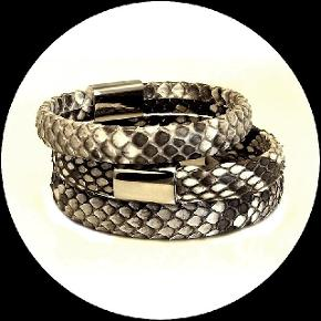 """Smukke & unikke armbånd i ægte python slangeskind Farve : Natur Materiale : Læder betrukket med ægte python slangeskind med blankpoleret magnetisk stål lås.  Skind bredde : 11 mm - ovalt m. runde kanter    Super lækkert og rustikt ByJega armbånd i kraftigt python slangeskind, monteret  med en tidsløs stål lås.  Armbåndet går én gang om håndleddet.   Størrelsesvalg :     XS  (længde 17,5 cm / håndledsstr. 15 cm) M   (længde 19,5 cm / håndledsstr. 17 cm) L   (længde 20,5 cm / håndledsstr. 18 cm)  Vejl. pris kr. 299,-/stk.    NU KUN kr. 250,-  Smykket lev. i organza pose samt æske med """"ByJega"""" logo  --------------------------------  Da der er tale om rest modeller, vil der kun være få mulige stk. og størrelsesvalg tilbage.  Jeg vil løbende lægge nye annoncer op med nye rest smykker / modeller fra brandet ByJega   Hvordan finder jeg størrelsen på mit armbånd ?   Mål dit håndled hvor det er bredest, eller hvor du normalt vil bære dit armbånd. Ved at måle på det bredeste sted sikre du at dit armbånd ikke bliver for stramt og kan glide frit på armen. Målet du skal bruge, skal være et tæt mål, dog ikke stramt."""