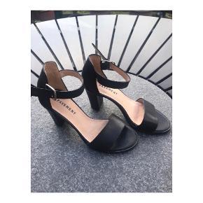 Enkle højhælede sandaler med hæl fra Pavement i str. 37. Er tager i brug en enkelt aften, standen er derfor mere eller mindre lig ny. Sandalerne er i læder og i lækker kvalitet, sidder godt på fødderne og selve modellen, er en tidsløs én af slagsen. Np: 899 kr.   Mp: se prisen plus evt. porto og gebyrer  Tag også gerne et kig på mine MANGE andre annoncer. Sælger ud af en masse lækre ting og sager.