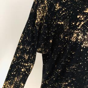 Flot kjole fra Nü i sort med guldglimmer.  Ærmerne er 3/4 lange.  Længde fra skulder er 90 cm, brystmålet er 110 cm, og taljen måler 96 cm.  Fremstillet af 97% vicscose og 3% elastan.  Aldrig brugt - mærke sidder stadig i.
