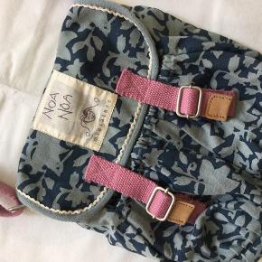 Supersød taske i kanvas fra Noa Noa Miniature. Med trykknapper, to lommer og et indvendigt lynlås-rum. Mål: 26x28 cm. Den justerbare rem er ca. en meter lang i alt på sit længste, og tasken kan bruges både som skuldertaske og crossbody.  Standen er som ny.  Sender gerne.