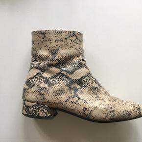 Beige slangepræget læderstøvler fra Vagabond i str 39. 🐍. Støvlen har en 70'er pasform og sidder tæt ind til læggen. Nogle steder er skindet ridser, men det ses ikke pga mønstret - derfor den lave pris.