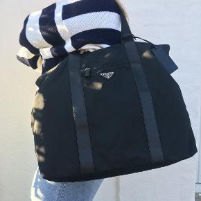 Mega lækker sort nylon prada taske. Perfekt til hverdags og som rejsetaske, stor og med plads til alt i den.  Prada tasken er i mega god stand, og har næsten ikke hvert brugt.   Taskens mål  brede: 44 cm højde : 40 cm dybde : 13 cm  håndtag : 59 cm  Der hører ikke noget med til tasken.