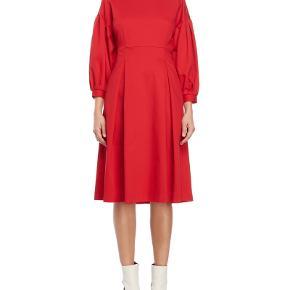 Rød Norr kjole med ballonærmer. Modellen hedder maggie.